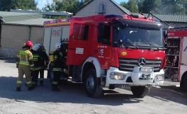 Strażacy przy samochodzie bojowym