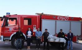 Delegacja na tle samochodu strażackiego
